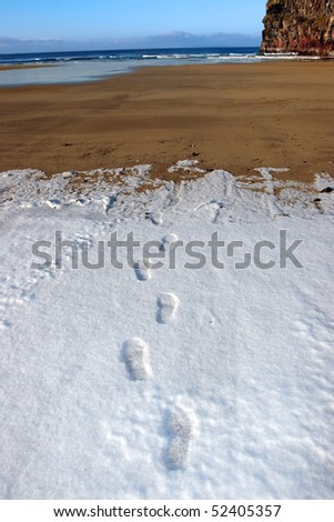 footprints on an empty beach with cliffs on a cold winters day - stock photo