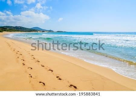 Footprints on beautiful sandy Chia beach and turquoise sea water, Sardinia island, Italy - stock photo