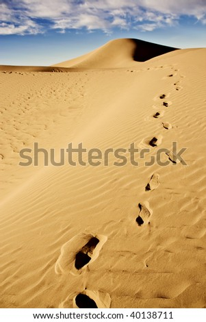 footprints on desert sand dunes with cloudy blue sky - stock photo