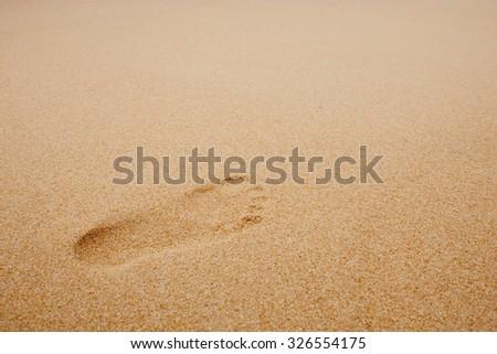 Footprints on sand beach - stock photo