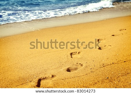 Footprints on sand beach along sea at dawn - stock photo