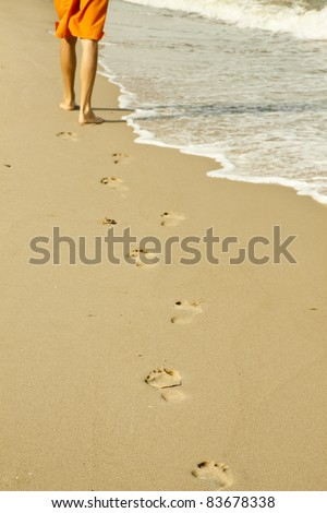 Footprints on sand beach along sea at dawn