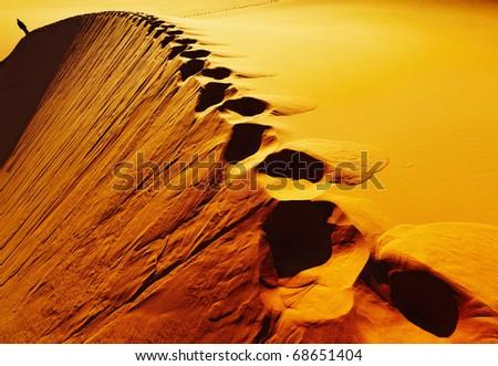 Footprints on sand dune, Sahara Desert, Algeria - stock photo