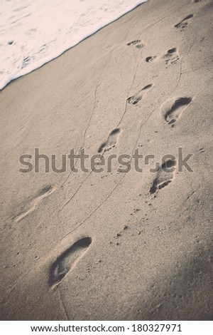 Footprints on the beach, filtered instagram style - stock photo