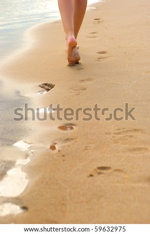 Footprints on the beach left behind - stock photo