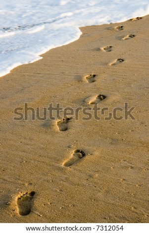Footprints on the beach with some waves coming in.
