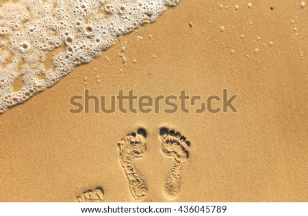 Footprints on the sand beach - stock photo