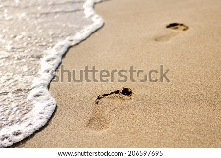 footprints on the sand of the beach at dawn - stock photo