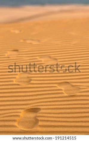 Footprints on the sand waves as background - stock photo