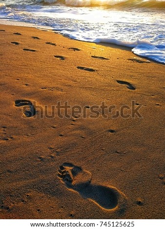 Footprints on the sand. White foam and golden beach.