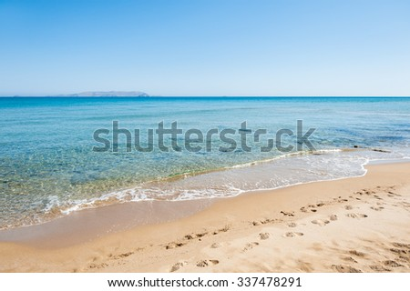 Footprints on the sandy beach. Beautiful tropical beach with turquoise water and white sand. Crete island, Greece - stock photo