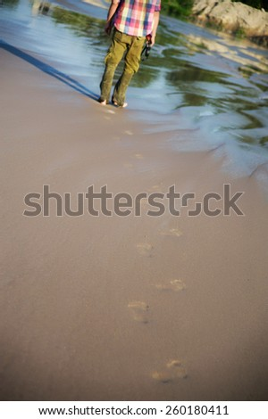 footprints on the wet sand from the male legs on the beach - stock photo