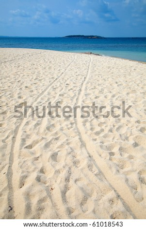 Footprints on white sand beach with blue sky - stock photo
