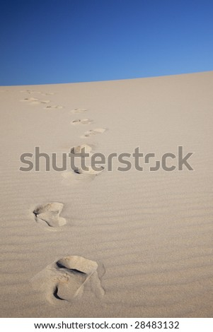 footprints uphill in middle of desert