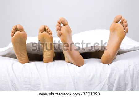 Foots of young couple lying in bed. Gray background, front view