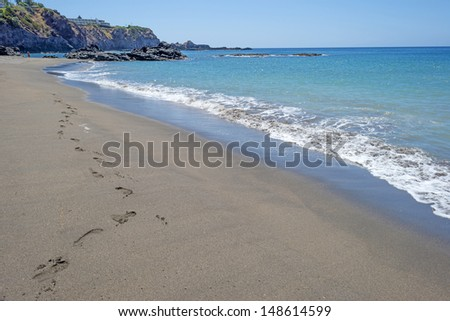 Footsteps at the beach of an island - stock photo