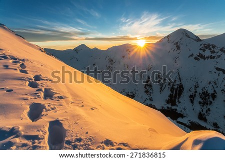 Footsteps in deep snow at sunset on a mountain peak in winter - stock photo