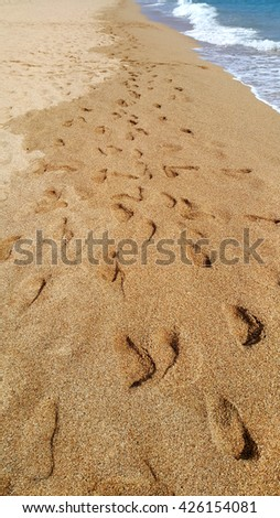 Footsteps in the sand at the beach - stock photo