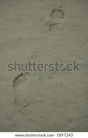 Footsteps in the sand.  Focus is on the closest footprint with the second footprint in the distance blurring out. - stock photo
