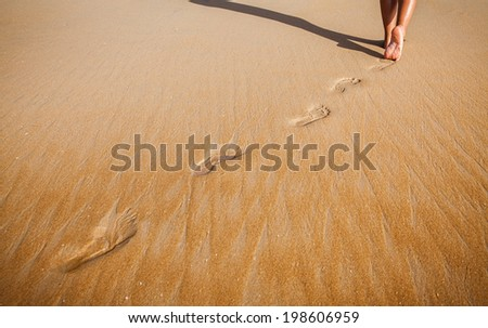 Footsteps in the sand of a nice beach. - stock photo