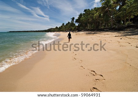 Footsteps of a Girl Walking on a Beach Shore - stock photo