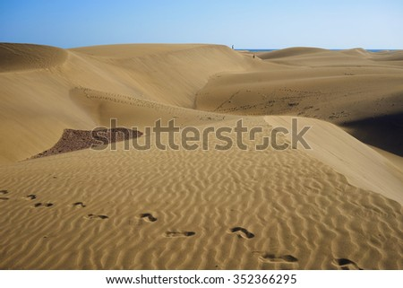 Footsteps on dunes in desert under blue sky /  Large sandy dunes in a wide dessert of Gran Canaria with footsteps / lost in the wilderness