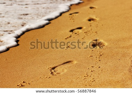 Footsteps on the beach . - stock photo