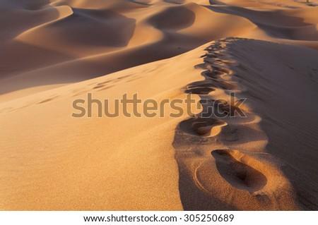 Footsteps on the sand dunes, Morocco, Erg Chebbi - stock photo