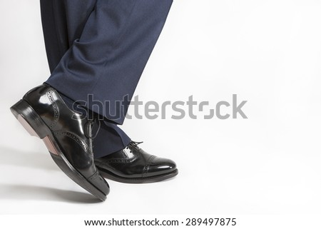 Footwear Concept: Closeup of Stylish Black Shiny Male Semi-Brogue On Crossed Legs Against White. Horizontal Image Orientation - stock photo