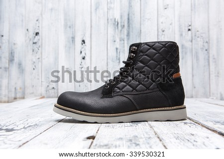 Footwear concept. Winter black men's shoe represented on white wooden background. One boot with white sole. - stock photo