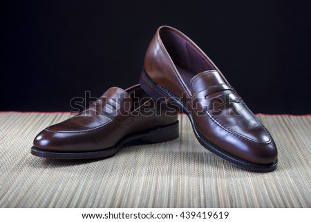 Footwear Concepts and Ideas. Pair of Stylish Expensive Modern Calf Leather Brown Penny Loafers Shoes.Closeup Shot. Horizontal  Image - stock photo