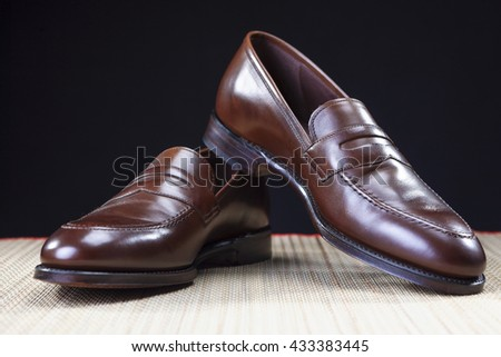 Footwear Concepts. Pair of Stylish Brown Penny Loafer Shoes Placed on Straw Surface against Black.Horizontal Shot - stock photo