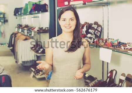 Footwear shop girl posing with different shoes and smiling