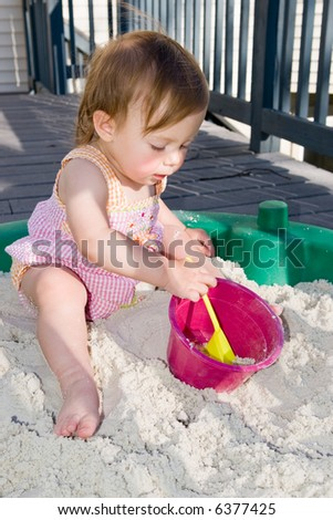 For babies aged one to two, everything is a learning experience. This little girl is very curious and busy as she plays in her sandbox with a shovel and pale.