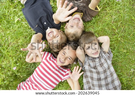 For happy kids on grass in summer day - stock photo