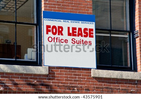 For Lease Office Suites blue and white sign on old brick office building between two windows. Room for your text on sign. - stock photo