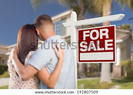 For Sale Real Estate Sign and Military Couple Looking at Nice New House. - stock photo
