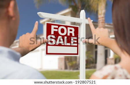 For Sale Real Estate Sign, House and Military Couple Framing Hands in Front. - stock photo