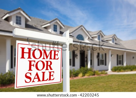 For Sale Real Estate Sign in Front of Beautiful New Home - stock photo