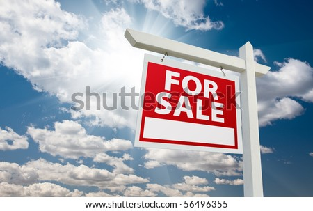 For Sale Real Estate Sign over Clouds and Blue Sky with Sun Rays. - stock photo