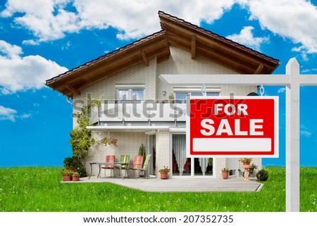 For sale sign in front of beautiful new house - stock photo