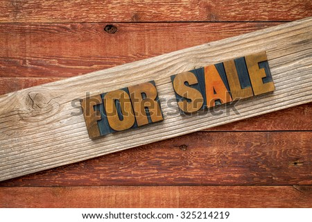 For sale sign - text in letterpress wood type over a grained cedar plank against rustic barn wood - stock photo