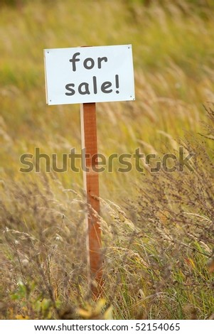 For sale signboard on a piece of ground - stock photo