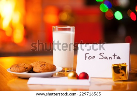 For Santa. Close-up of cookies and glass of milk on the table with Christmas Tree and fireplace in the background  - stock photo