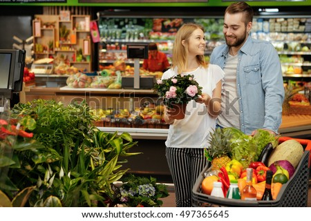 For the cozy home. Shot of a beautiful happy woman shopping at the supermarket with her boyfriend, cheerful woman holding potted flower smiling to her boyfriend