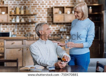 For you. Pleasant caring aged woman helping her kind elderly husband by giving him a glass of water while being at home