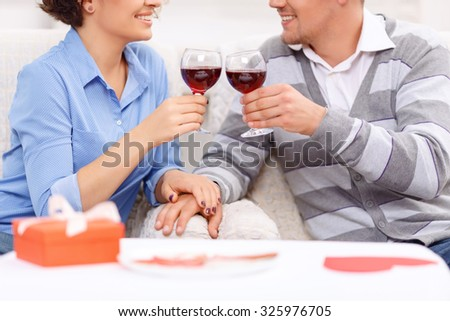 For you. Pleasant vivacious young loving couple holding glasses and drinking wine while sitting at the table - stock photo