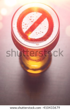 forbidden symbol on foam in beer glass on black table, view from above