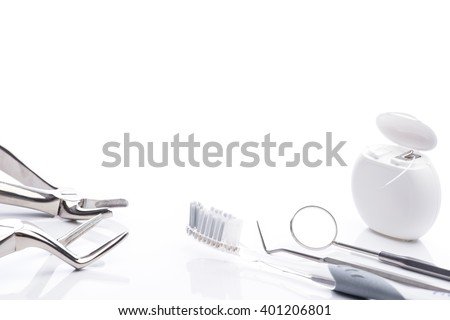 Forceps, toothbrush, dental floss, mouth mirror and dental probe on white surface - stock photo