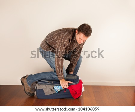 forcing the last few pieces of clothing into an over-full suitcase - stock photo